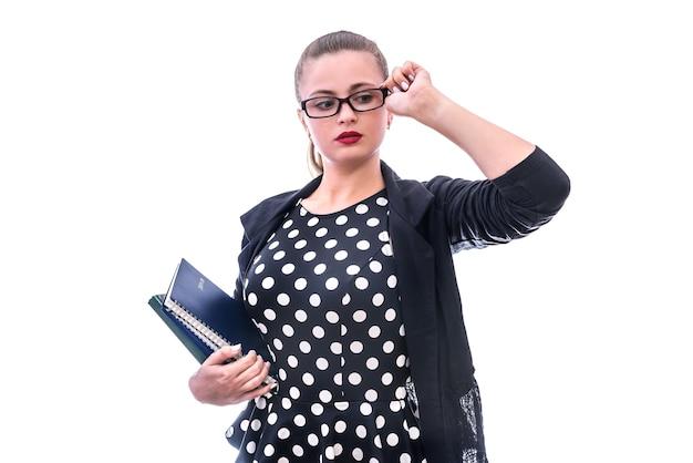 Młoda kobieta w okularach trzymając książki na białym tle