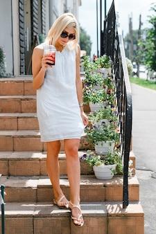 Młoda kobieta w okularach, trzymając świeży sok i stojąc na kroku na zewnątrz. blondynka w sukni z białą wstążką