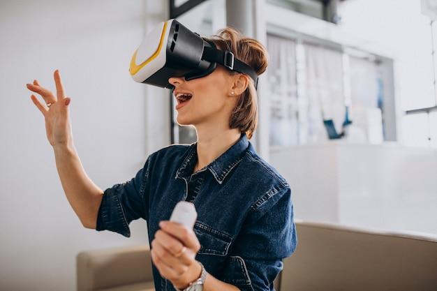 Młoda kobieta w okularach vr i gry wirtualnej za pomocą pilota