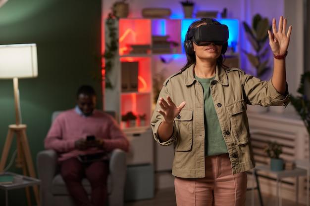 Młoda kobieta w okularach vr stojąc i gestykuluje, grając w wirtualnej rzeczywistości