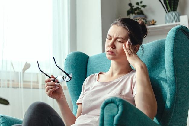 Młoda kobieta w okularach w rękach siedzi na krześle i cierpi