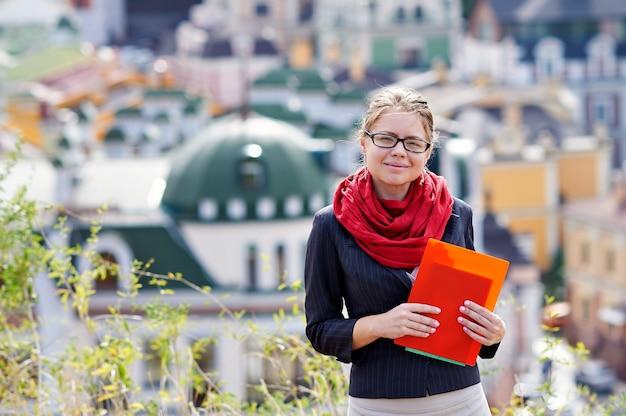 Młoda kobieta w okularach z folderem w ręce