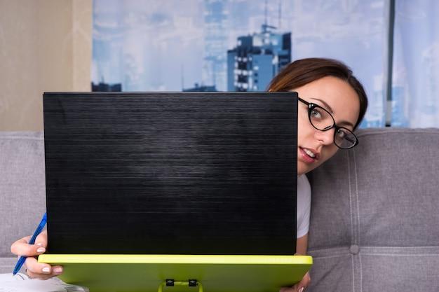 Młoda kobieta w okularach zerkająca zza laptopa, pracująca na laptopie, prowadząca interesy z domu, trzymająca długopis, gdy czyta informacje na ekranie
