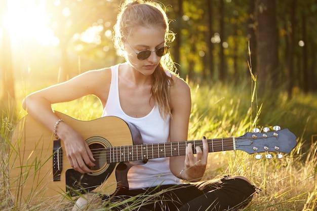 Młoda kobieta w okulary gra na gitarze siedząc