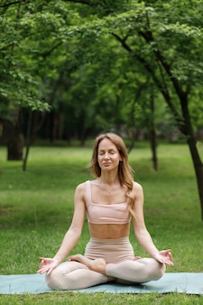 Młoda kobieta w parku latem zaangażowana w jogę i medytację
