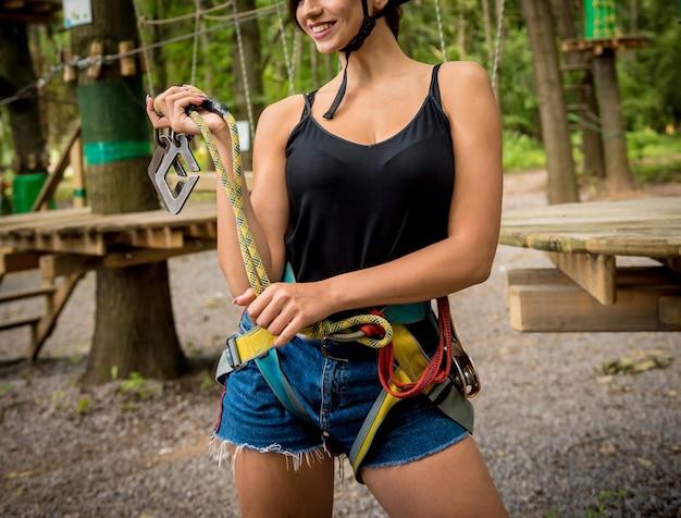 Młoda kobieta w parku linowym przygody. sprzęt do wspinaczki.