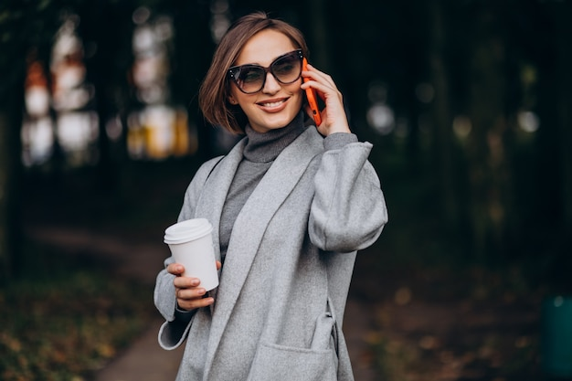 Młoda kobieta w parku pije kawę i rozmawia przez telefon