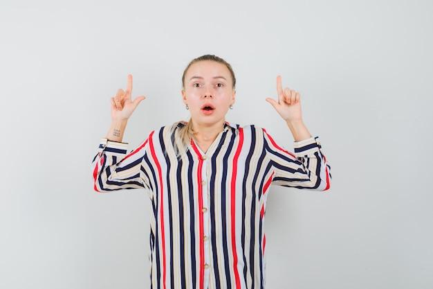 Młoda kobieta w pasiastej bluzce pokazująca przegrane gesty obiema rękami i wyglądająca na zaskoczoną