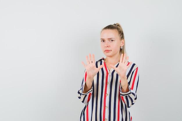 Młoda kobieta w pasiastej bluzce pokazuje gesty stopu obiema rękami i wygląda na przestraszoną