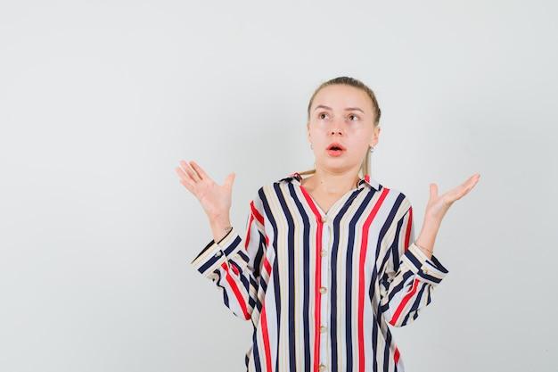 Młoda kobieta w pasiastej bluzce wzrusza ramionami i podnosi obie ręce i wygląda na zaskoczoną