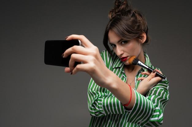 Młoda kobieta w pasiastej bluzce za pomocą czarnego telefonu komórkowego zamiast lustra i nakładania makijażu z pędzlem na białym tle