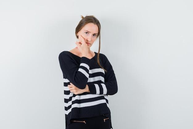 Młoda kobieta w pasiastej dzianinie i czarnych spodniach, opierając policzek na dłoni i stojąc w myślącej pozie i wyglądając poważnie