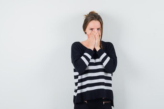 Młoda kobieta w pasiastej dzianinie i czarnych spodniach zakrywających usta i nos rękami i wyglądająca na zaskoczoną