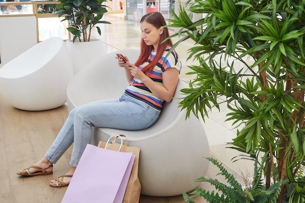 Młoda kobieta w pasiastej koszuli siedzi w centrum handlowym z torbami na zakupy, korzysta z telefonu komórkowego