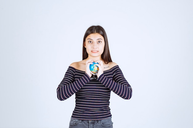 Młoda kobieta w pasiastej koszuli trzyma mini kulę ziemską między rękami