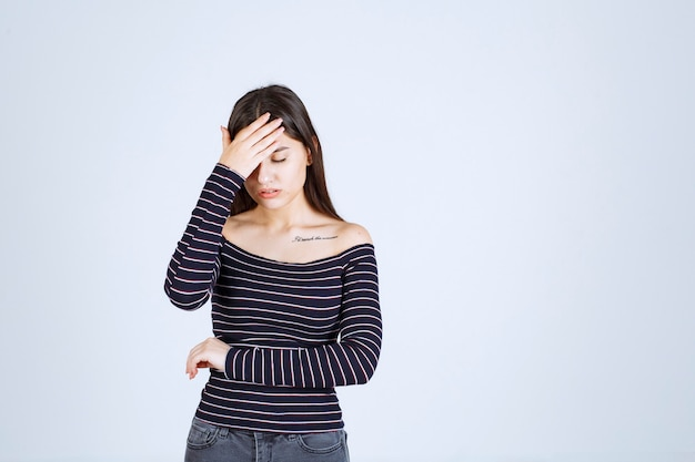 Młoda kobieta w pasiastej koszuli, trzymając głowę z powodu bólu głowy