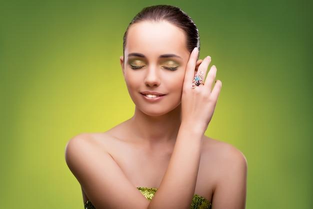 Młoda kobieta w piękna pojęciu na zieleni ścianie