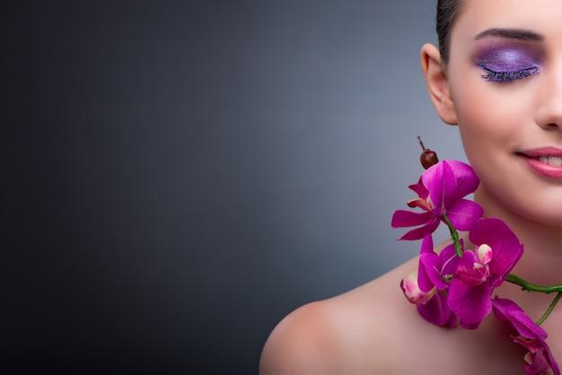 Młoda kobieta w piękna pojęciu z storczykowym kwiatem