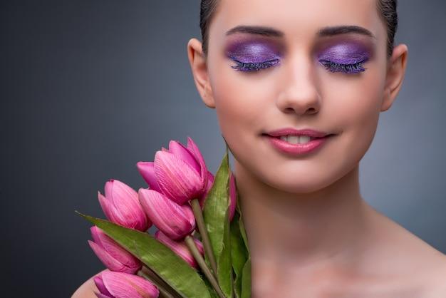 Młoda kobieta w piękna pojęciu z tulipanowym kwiatem