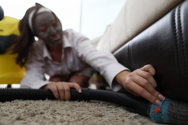Młoda kobieta w piękna zdroju masce używać vacuun cleaner przeciw domowemu tłu. koncepcja stylu życia