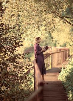 Młoda kobieta w pięknej sukience czyta książkę w letni słoneczny dzień leśny park dziewczyna relaksuje wolność na świeżym powietrzupionowy las beckground