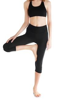 Młoda kobieta w pięknych spodniach do jogi na białej powierzchni