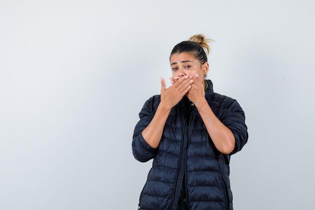 Młoda kobieta w pikowanej kurtce trzymając ręce na ustach i patrząc zdziwiona, widok z przodu.