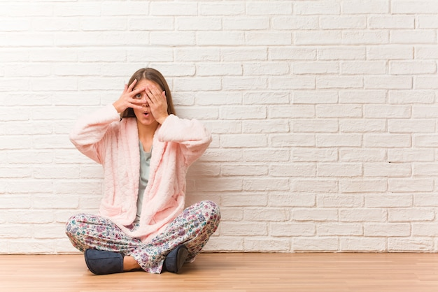 Młoda kobieta w piżamie czuje się zmartwiona i przestraszona