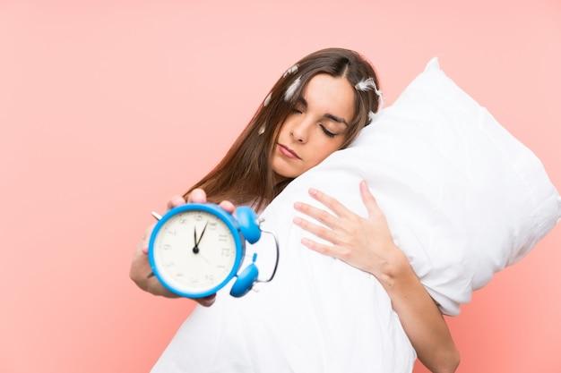 Młoda kobieta w piżamie gospodarstwa rocznika zegar