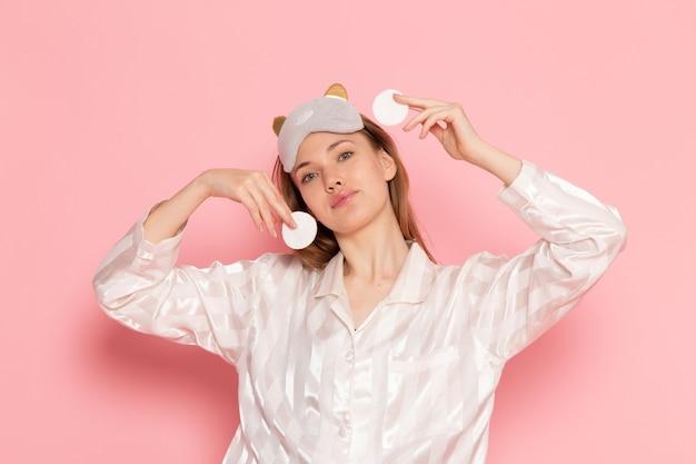 Młoda kobieta w piżamie i masce do spania czyszcząca twarz na różowo