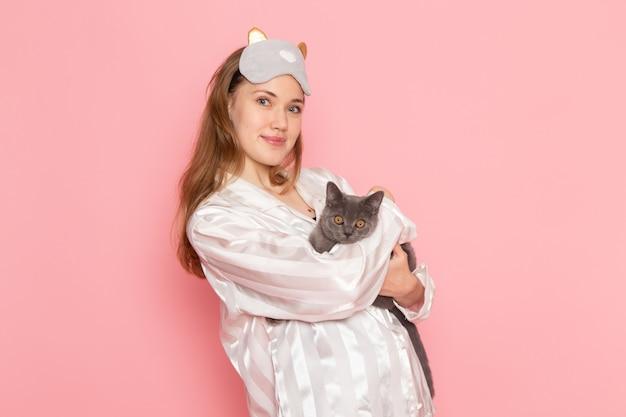 Młoda kobieta w piżamie i masce do spania pozuje z uśmiechem i szarym kotkiem na różowo