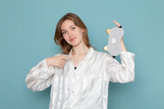 Młoda kobieta w piżamie i masce do spania, trzymając ją na niebiesko