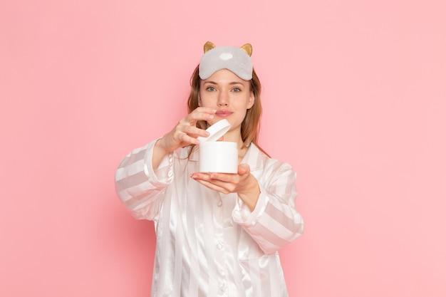 Młoda kobieta w piżamie i masce do spania, trzymając puszkę kremu na różowo