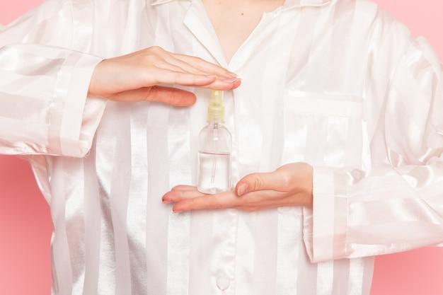 Młoda kobieta w piżamie i masce do spania, trzymając spray na różowo