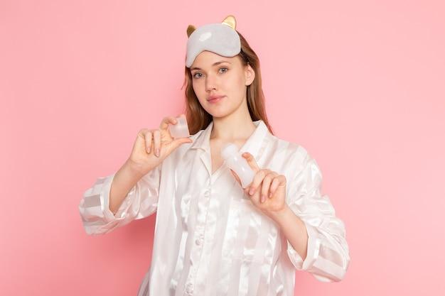 Młoda kobieta w piżamie i masce do spania, trzymając środek do czyszczenia makijażu na różowo