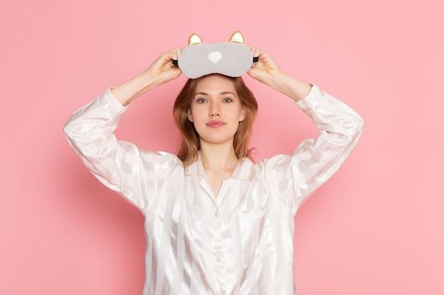 Młoda kobieta w piżamie i masce do spania uśmiechnięta na różowo