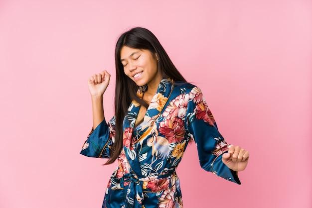 Młoda kobieta w piżamie kimono, taniec i zabawę.