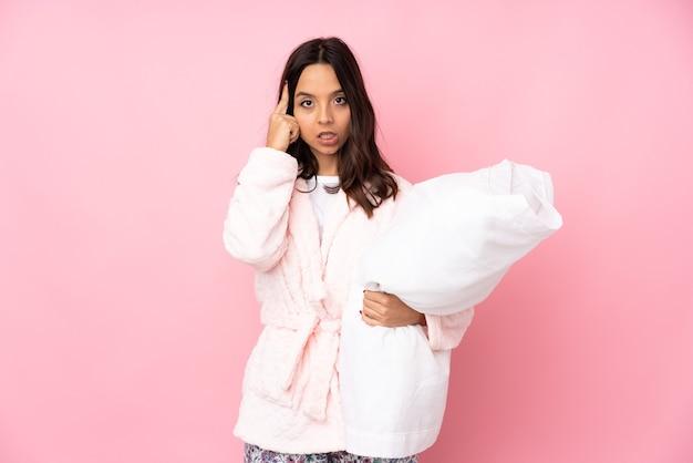 Młoda kobieta w piżamie na białym tle na różowym tle myśli pomysł