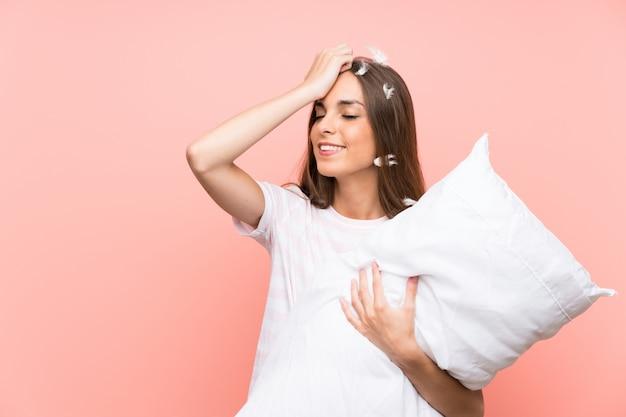 Młoda kobieta w piżamie na izolowanej różowej ścianie coś sobie uświadomiła i zamierza rozwiązać problem