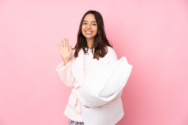 Młoda kobieta w piżamie na różowej ścianie pozdrawiając ręką z happy wypowiedzi