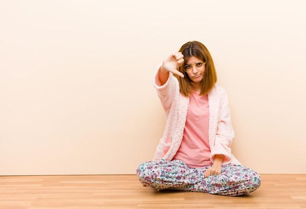 Młoda kobieta w piżamie siedząca w domu czuje się krzyża, zła, zirytowana, rozczarowana lub niezadowolona, pokazując kciuk w dół z poważnym wyrazem twarzy