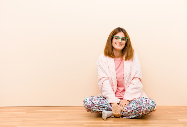 Młoda kobieta w piżamie siedząca w domu, wyglądająca na szczęśliwą i mile zaskoczoną, podekscytowana zafascynowanym i zszokowanym wyrazem twarzy