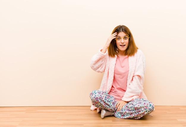 Młoda kobieta w piżamie siedząca w domu, wyglądająca na szczęśliwą, zdziwioną i zaskoczoną, uśmiechniętą i zdającą sobie sprawę z niesamowitych i niesamowitych dobrych wiadomości