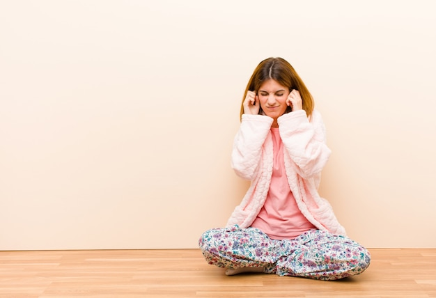 Młoda kobieta w piżamie siedząca w domu, wyglądająca na złą, zestresowaną i zirytowaną, zasłaniającą uszy ogłuszającym hałasem, dźwiękiem lub głośną muzyką