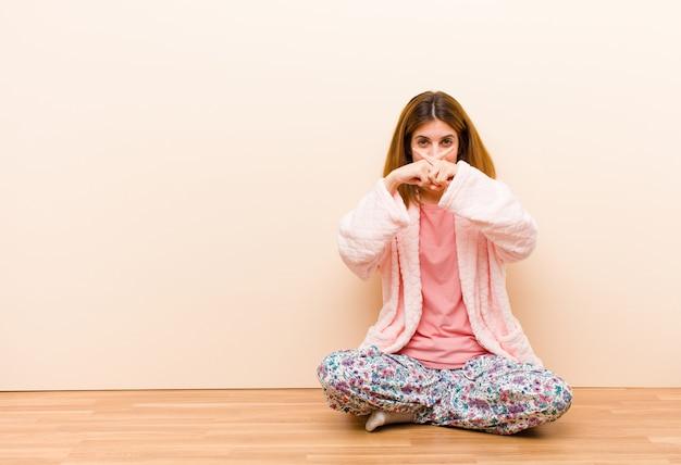 Młoda kobieta w piżamie, siedząca w domu, wyglądająca poważnie i niezadowolona, odrzucając oba palce z przodu, prosząc o ciszę