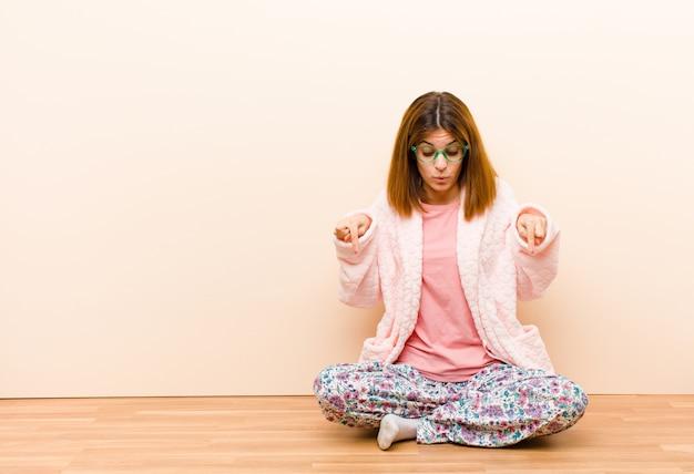 Młoda kobieta w piżamie siedząca w domu z otwartymi ustami obiema rękami skierowana w dół, wyglądająca na zszokowaną, zdumioną i zaskoczoną