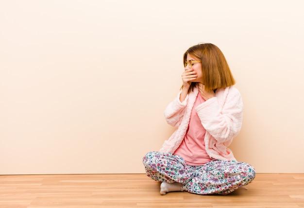 Młoda kobieta w piżamie siedzi w domu czując się chory z bólem gardła i objawami grypy, kaszel z zakrytymi ustami