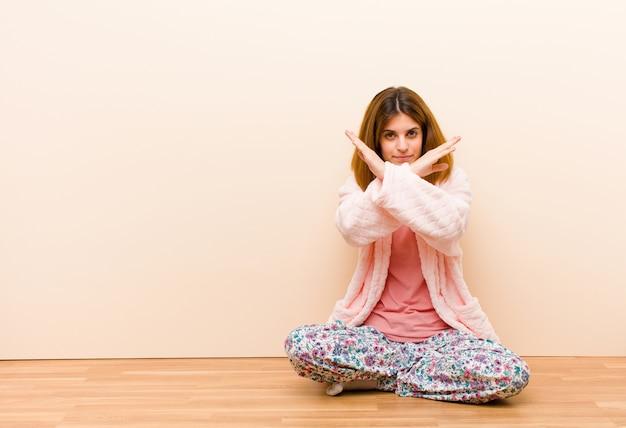 Młoda kobieta w piżamie siedzi w domu i wygląda na zirytowaną i dość swojej postawy, mówiąc wystarczająco dużo! ręce skrzyżowane do przodu, każąc ci przestać