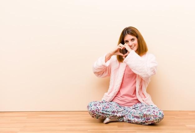 Młoda kobieta w piżamie siedzi w domu uśmiecha się i czuje się szczęśliwy, romantyczny i zakochany, co kształt serca obiema rękami