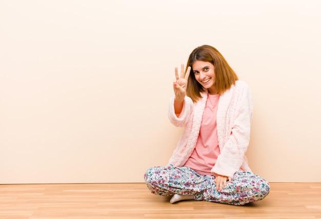 Młoda kobieta w piżamie siedzi w domu uśmiechnięty i przyjazny, pokazując numer trzy lub trzeci ręką do przodu, odliczając